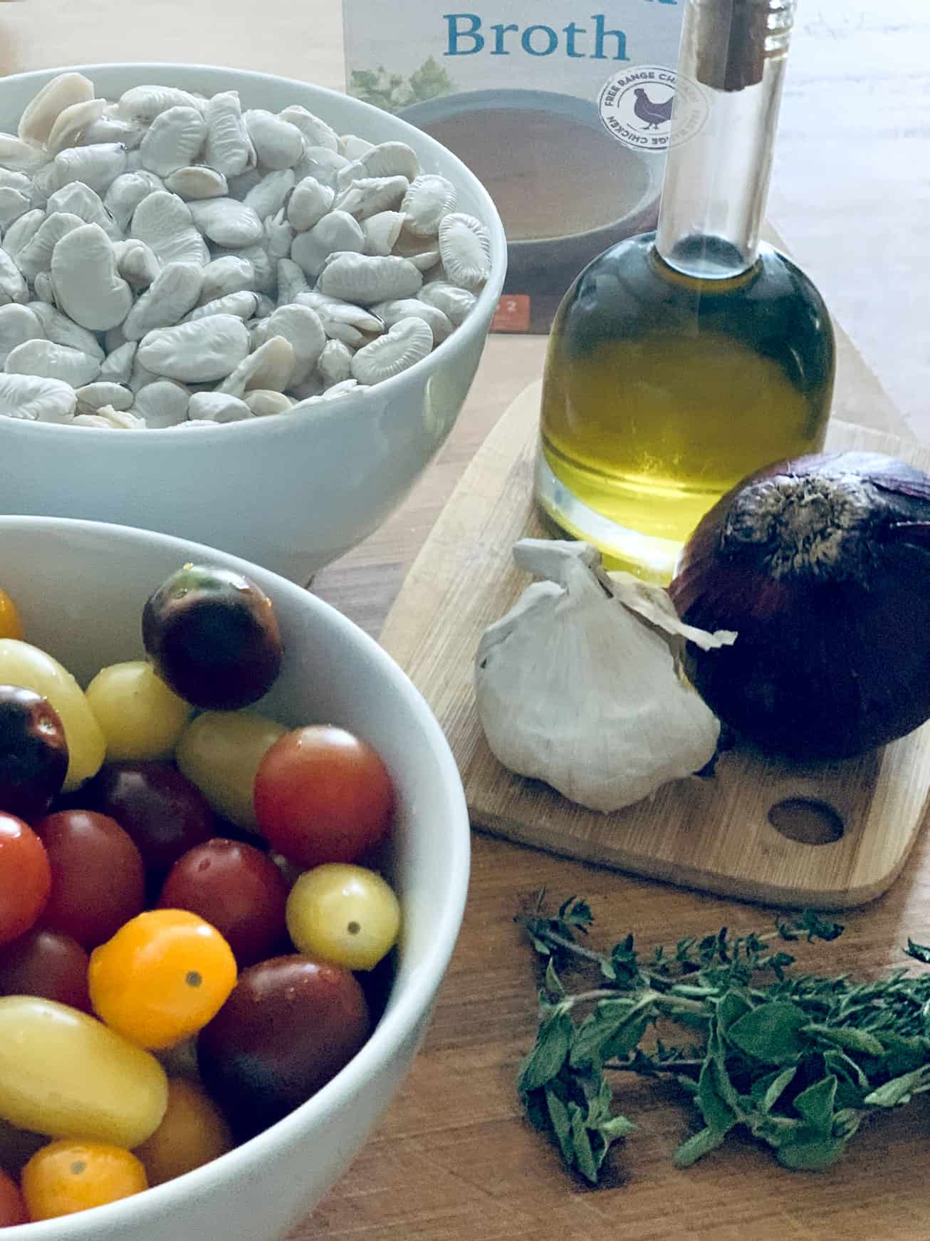 A bowl full of multi color cherry tomatoes, a head of garlic, a red onion, a bottle of olive oil, a bowl with giant beans, a box of chicken broth at the back and some fresh herbs at the front.
