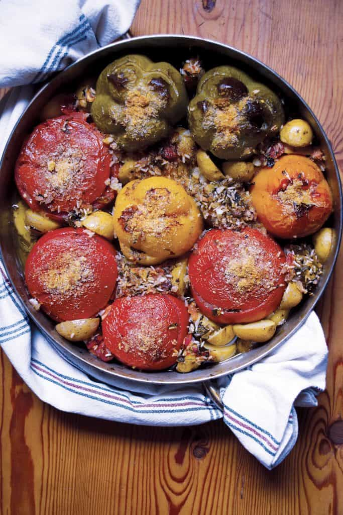 A round baking pan with tomatoes and peppers on a wooden table.