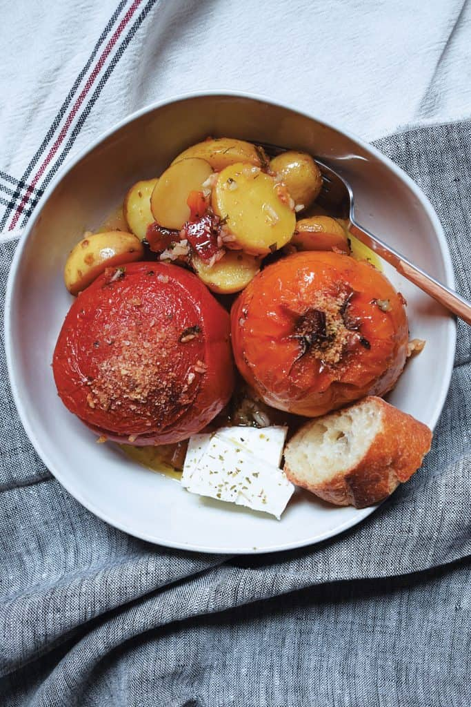 plate with a tomato and a bell pepper, stuffed with rice, potatoes, bread and feta cheese.