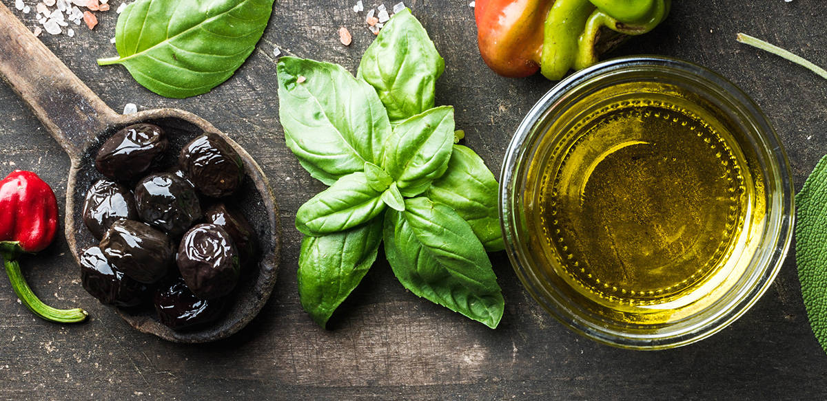 A wooden spoon filled with black olives, a small bunch of fresh basil, a glass jar with olive oil.