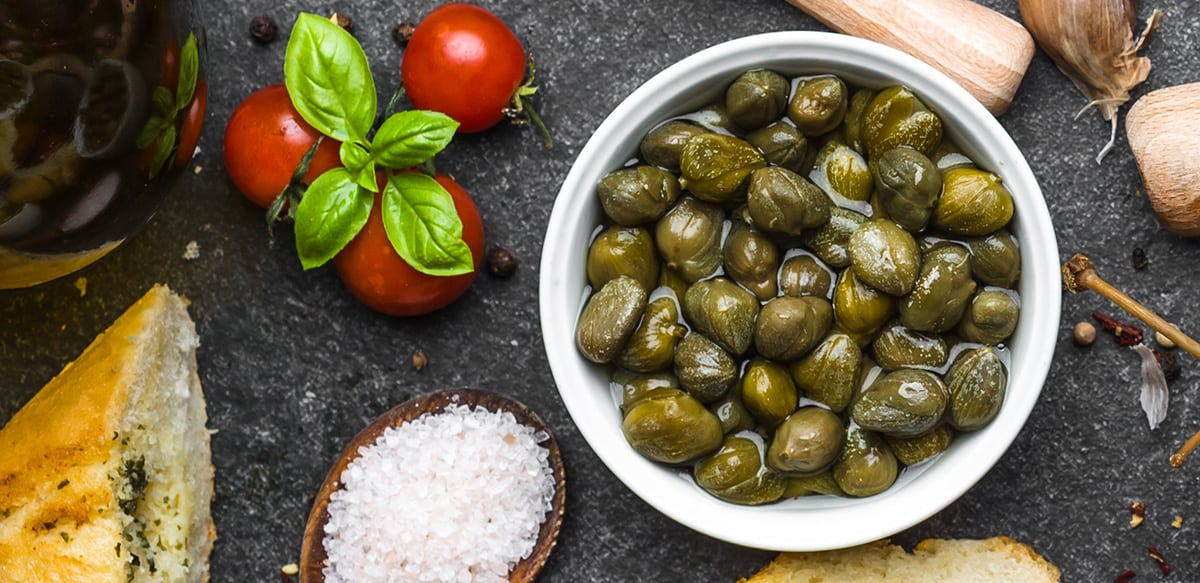 A bowl full of capers, 3-4 cherry tomatoes with fresh basil leaves on top slat and spices on a grey wood background.