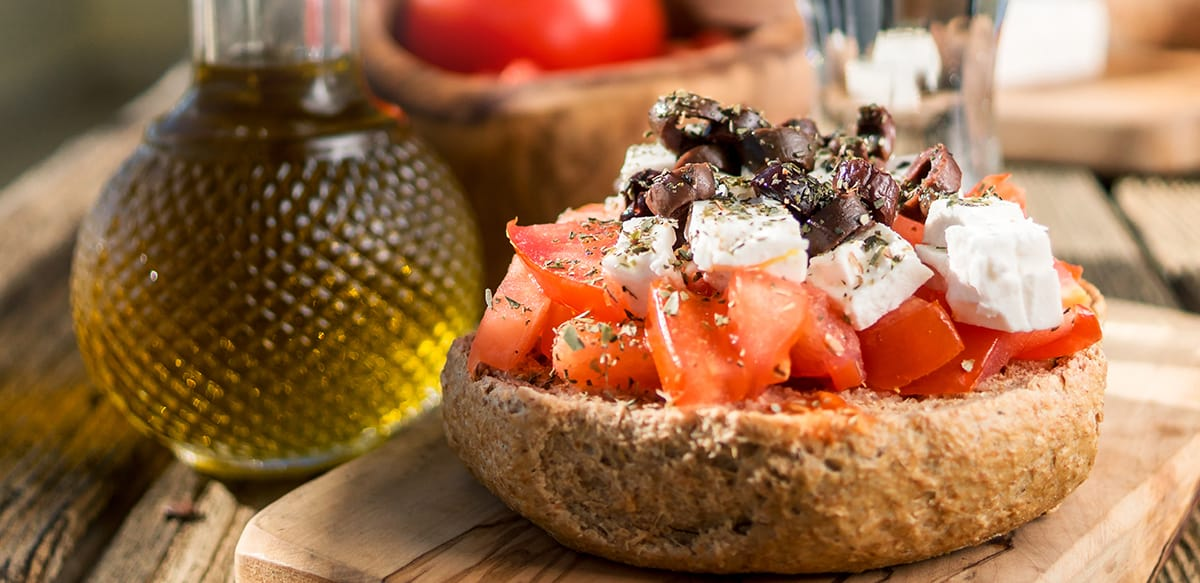A cretan rusk with tomatoes, feta and olives on top. On the left a small glass bottle with olive oil.