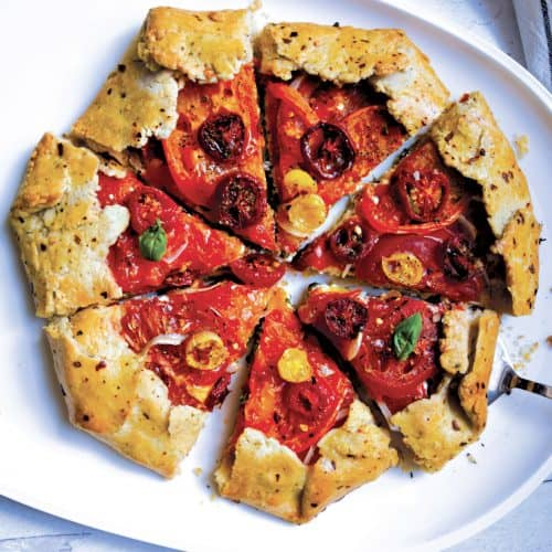 A galette filled with feta cheese, onions and lots of tomatoes on a platter, cut in pieces ready to be served.