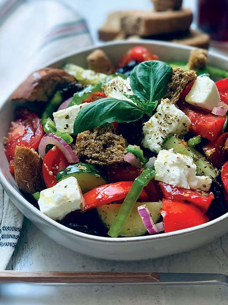 A Greek salad in a white plate with a serving spoon an olive oil bottle and fresh basil leave