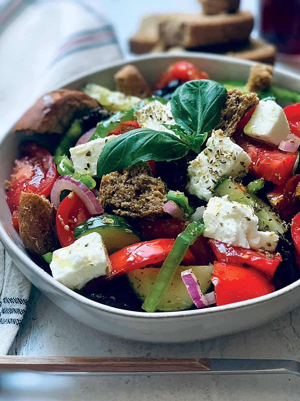 A Greek salad in a white plate with a serving spoon an olive oil bottle and fresh basil leaves.