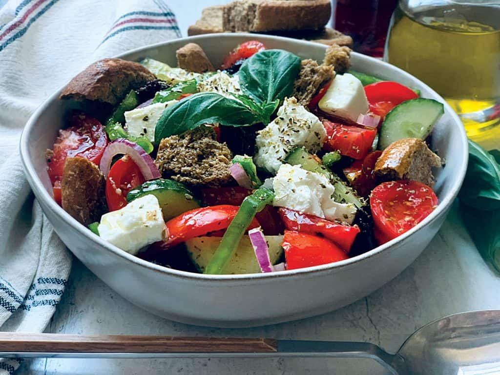 A Greek salad in a plate with a serving spoon, an olive oil bottle and fresh basil leaves.