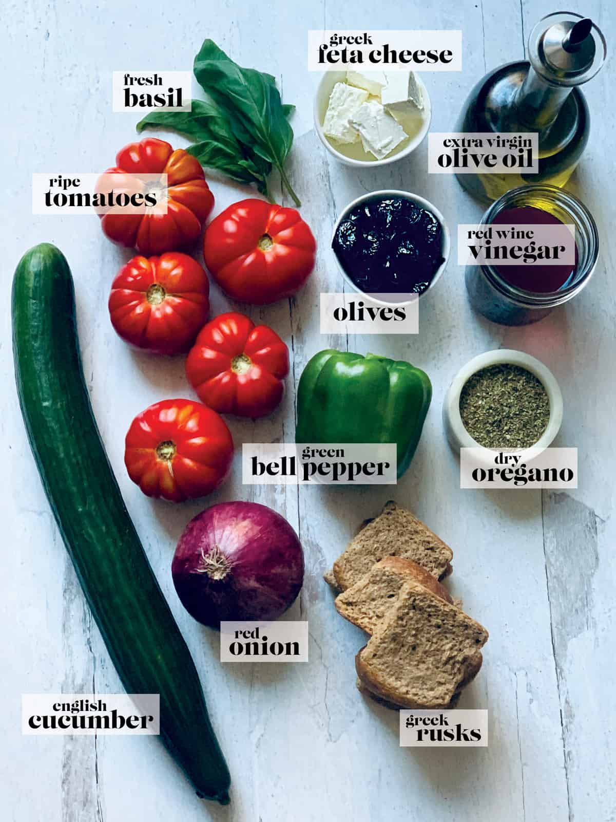 Tomatoes, a cucumber, a green bell pepper, an onion, fresh basil, containers with feta cheese, olives, oregano, and vinegar and a bottle of olive oil and some rusks on a table.