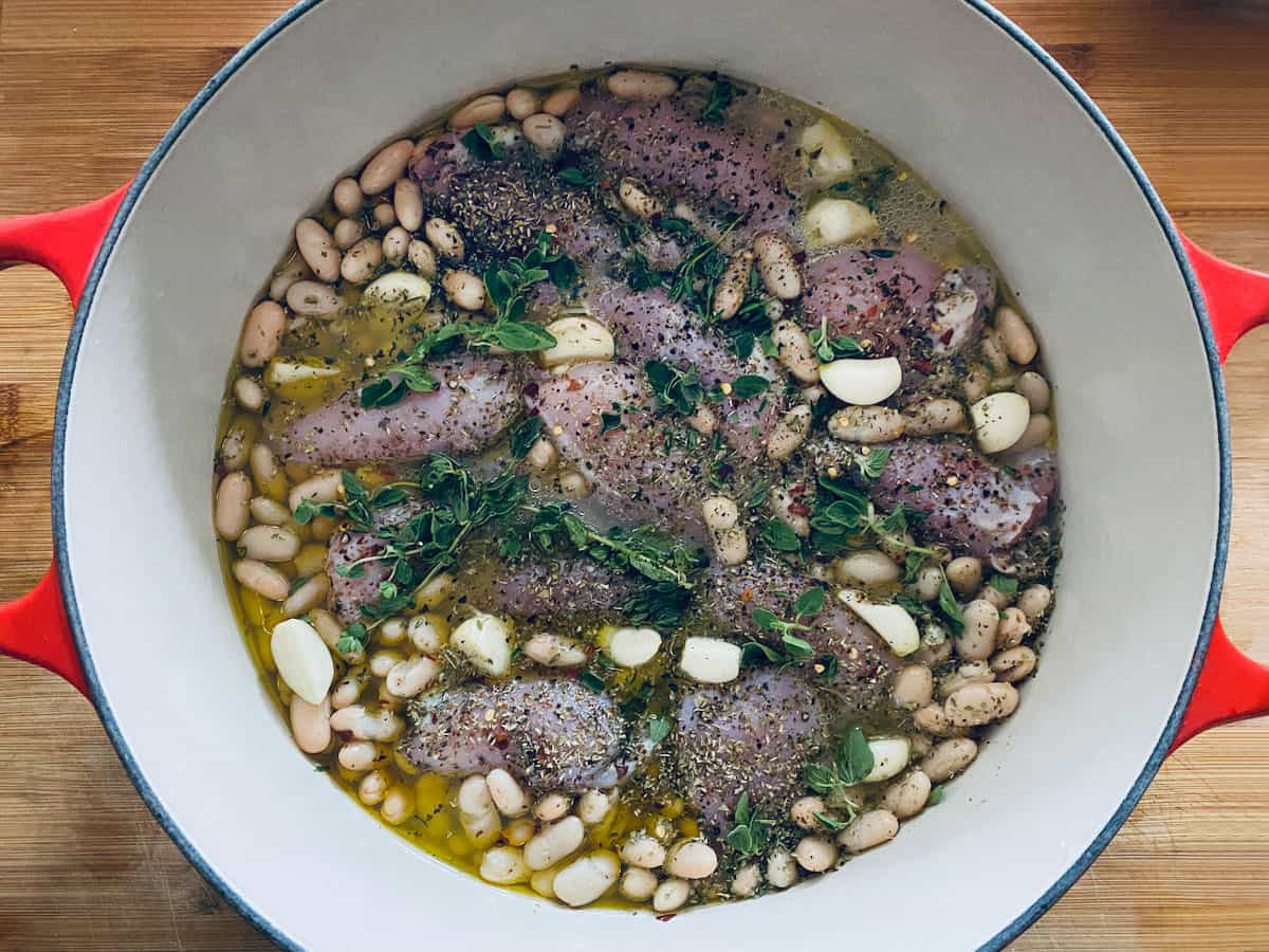 A red dutch oven with uncooked chicken thighs beans and herbs.