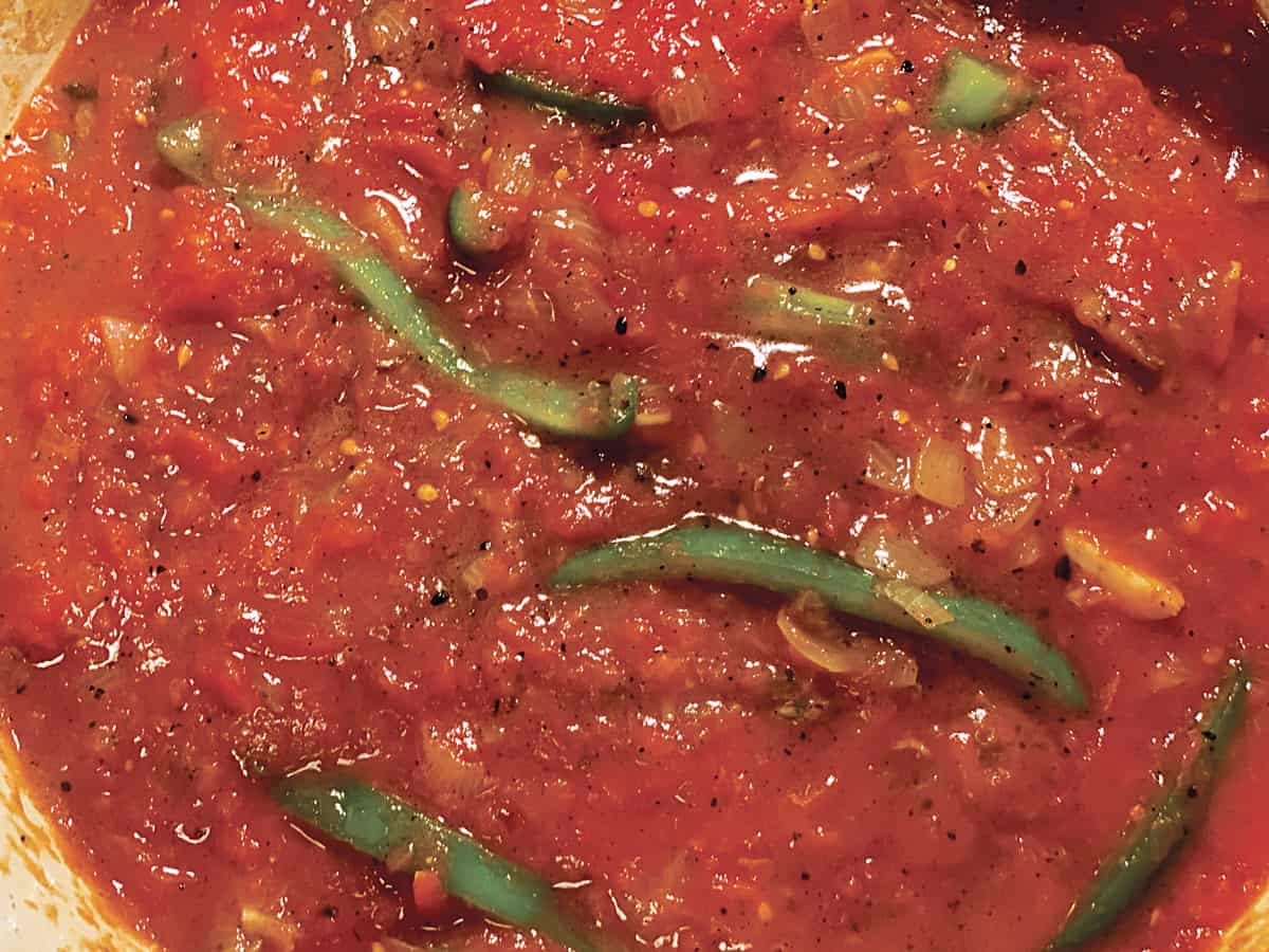 Tomato sauce with green bell pepper slices and onions.