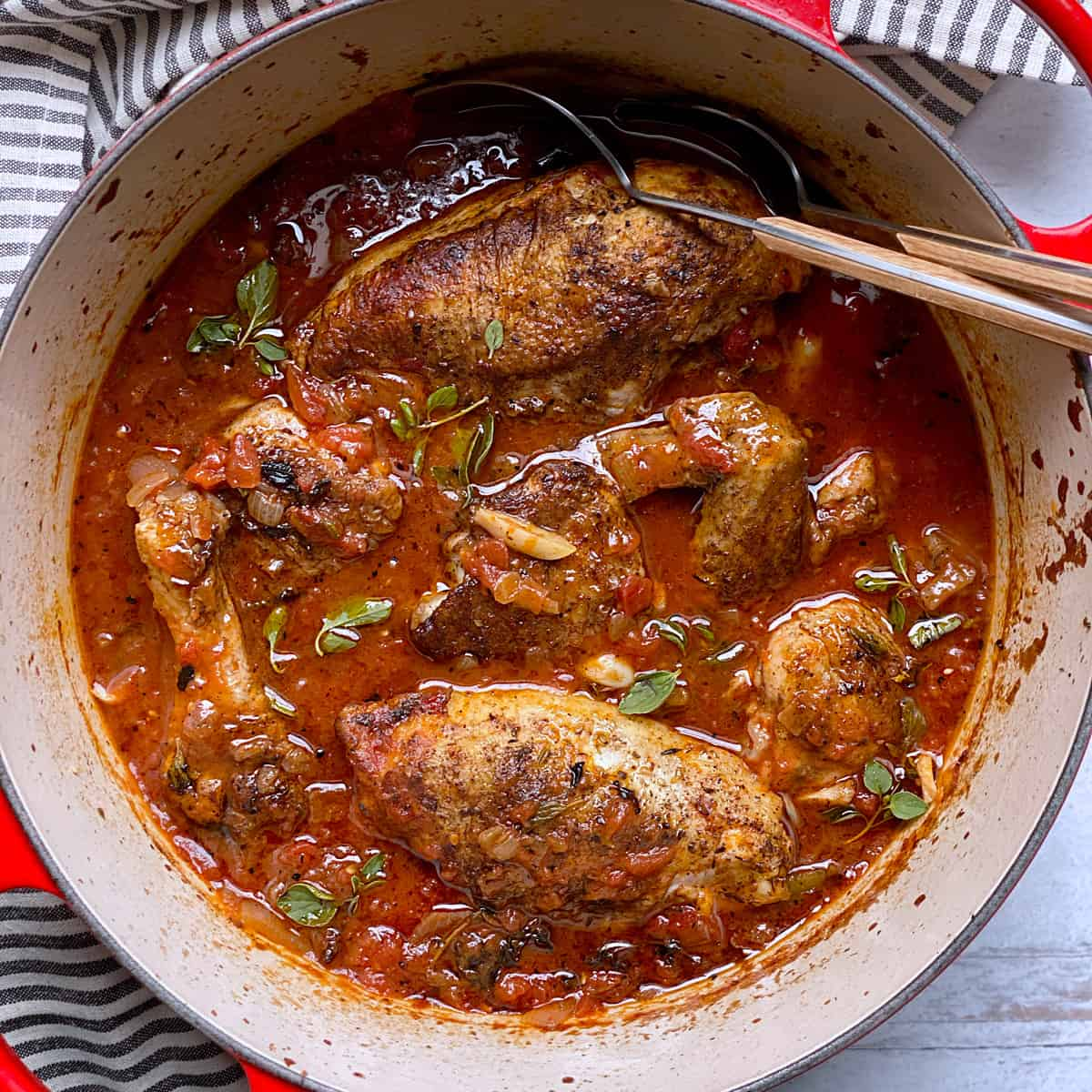 A red dutch oven with chicken in red sauce and two serving spoons.