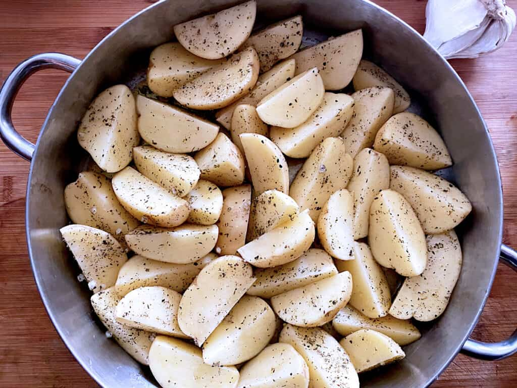 A large baking pan with raw potatoes.