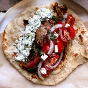 A plate with fillings for Greek souvlaki, a tzatziki bowl and tomato salad.