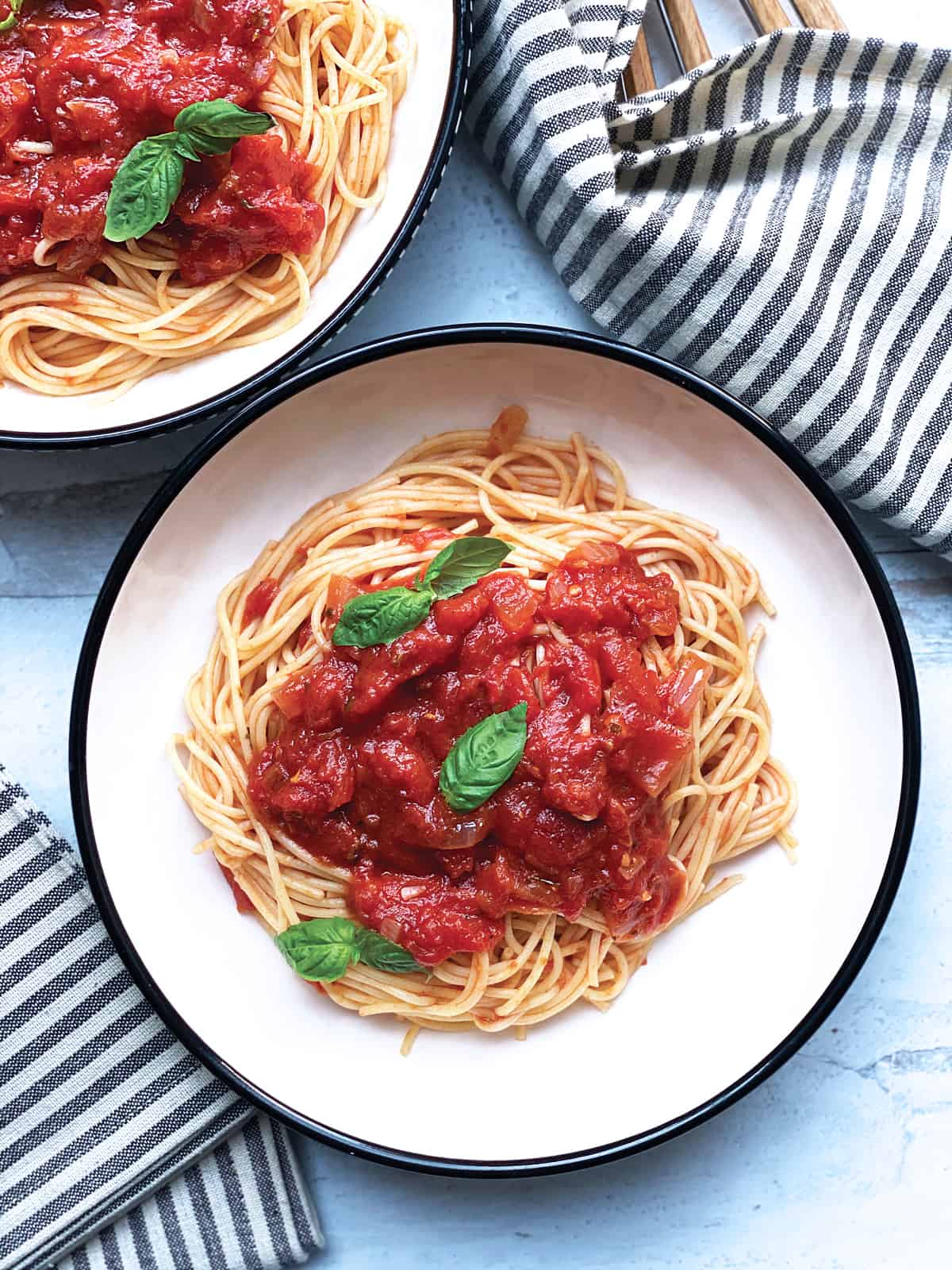 Two plates with spaghetti and greek tomato basil sauce.
