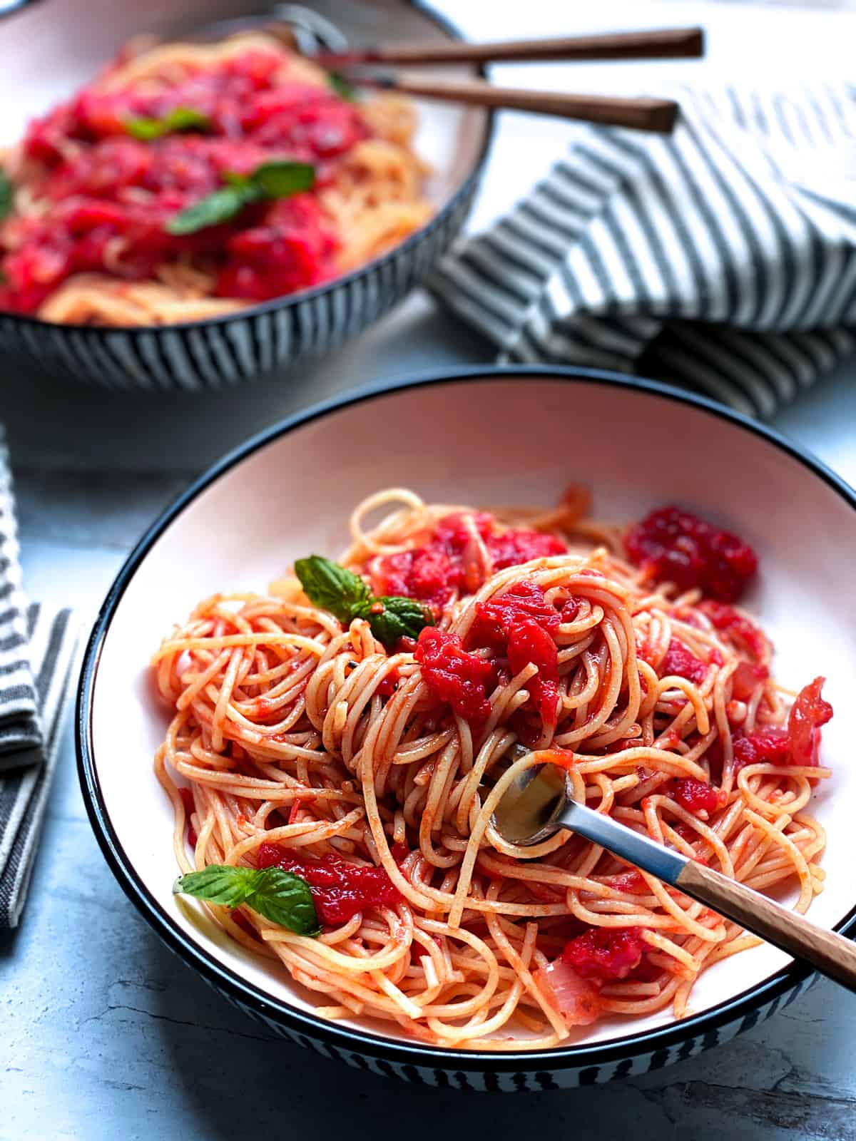 Two plates with spaghetti and tomato basil sauce.