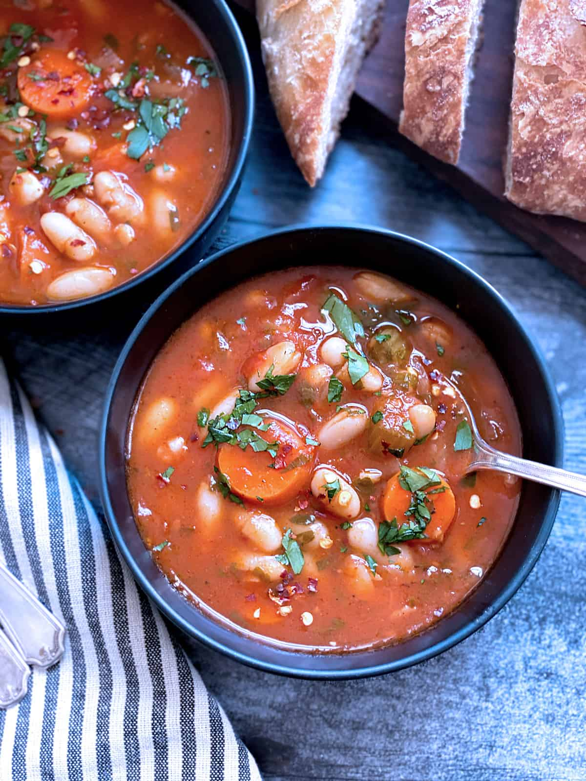 Two bowls with fasolada-greek white bean soup and bread.