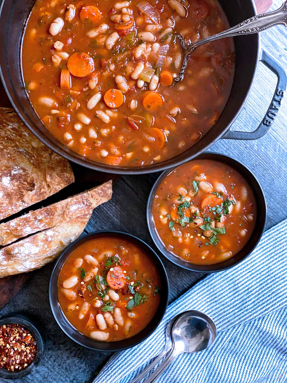 Two bowls with fasolada-greek white bean soup, bread and a pot filled with the soup.