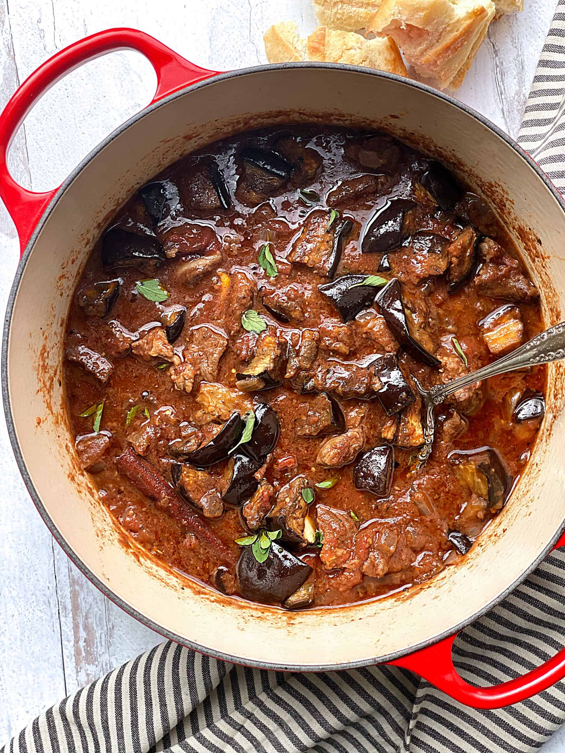 A red dutch oven with beef and eggplant stew