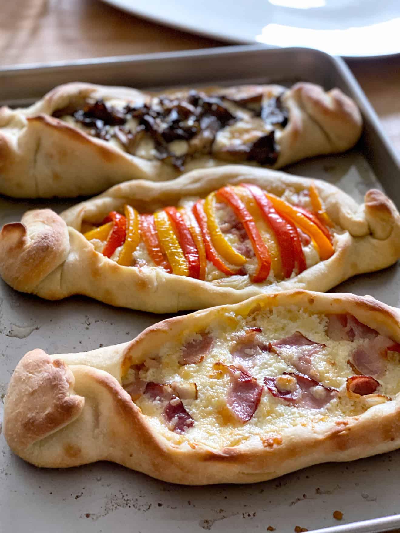 Three pizza boats on a baking sheet.