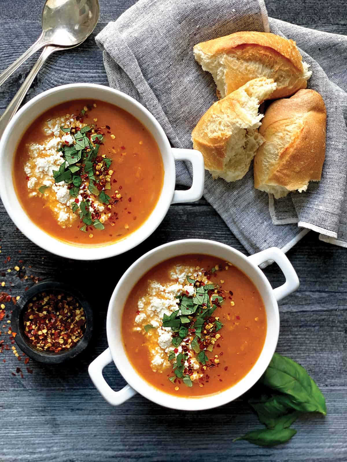 Two bowls with tomato soup with basil and feta, a cloth napkin, and bread on a table.