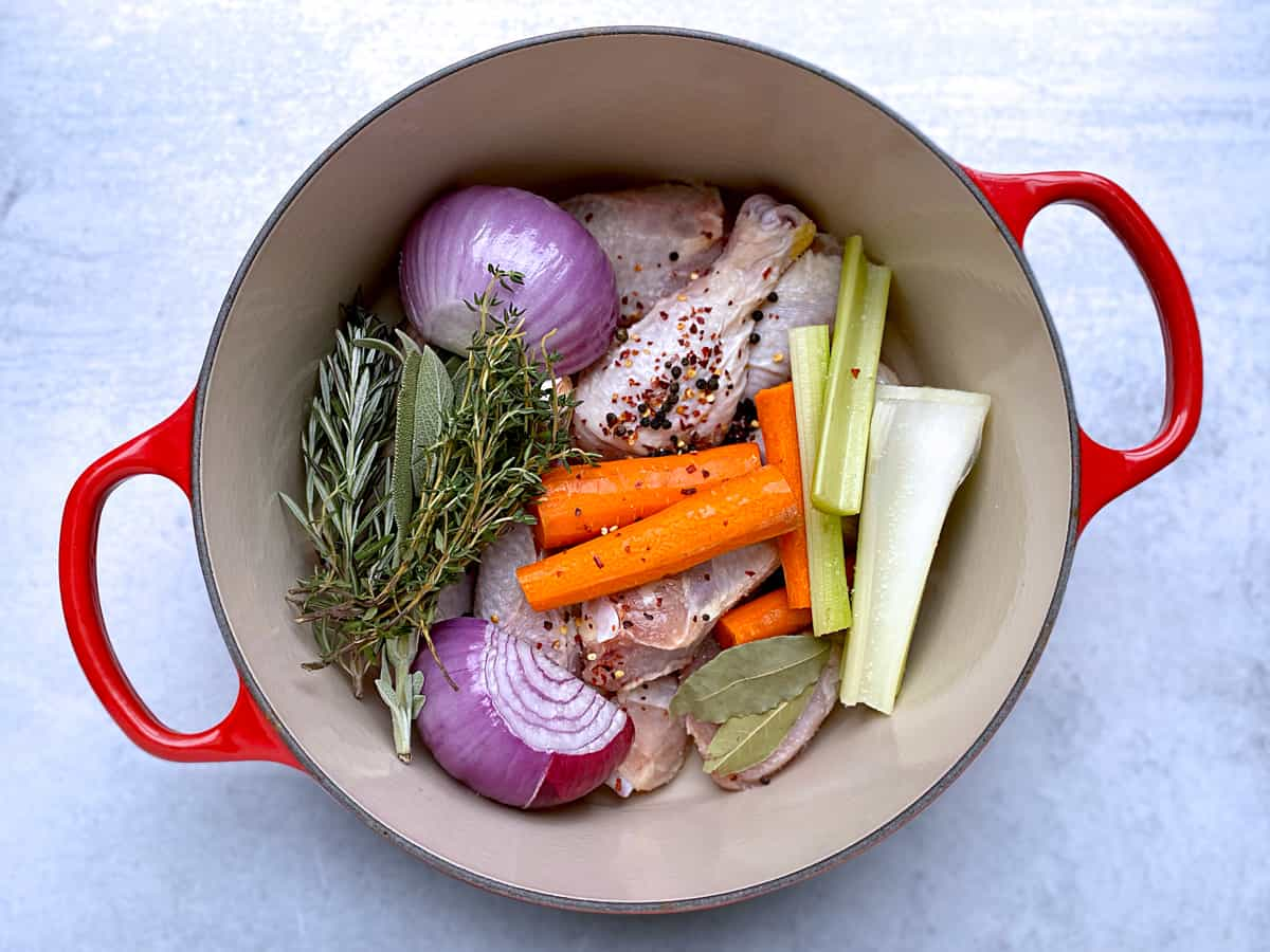 A red dutch oven with ingredients for chicken broth.