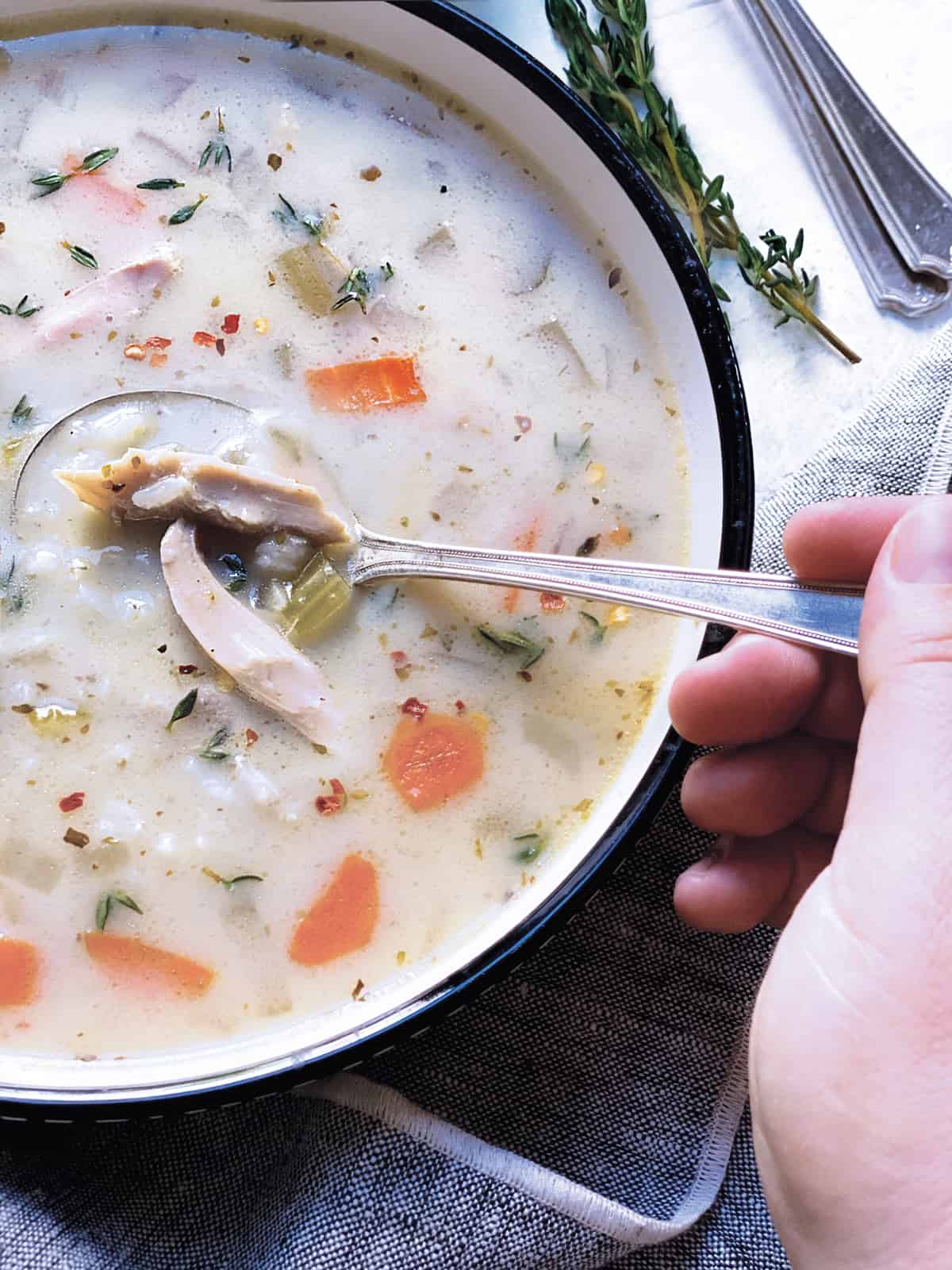 A bowl with lemon chicken soup and a hand holding a spoon.