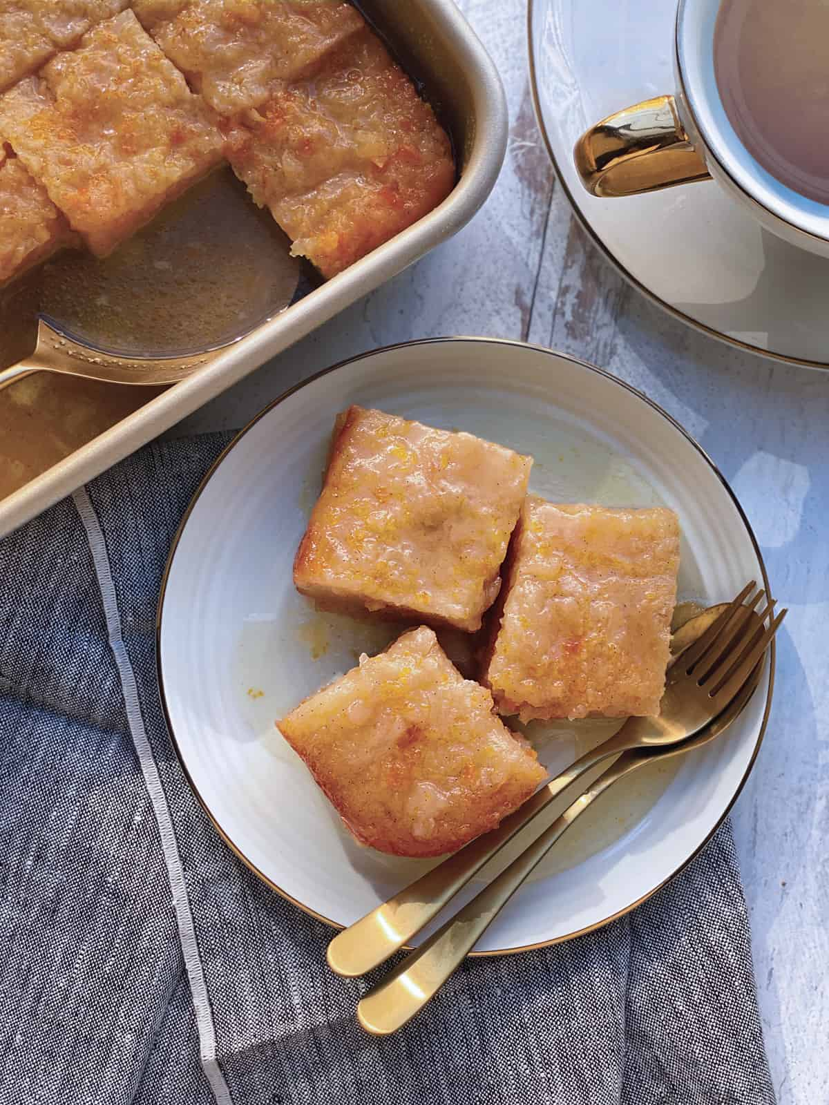 A plate with three pieces of greek orange phyllo cake utensils over napkin. A pan with cake at the back.