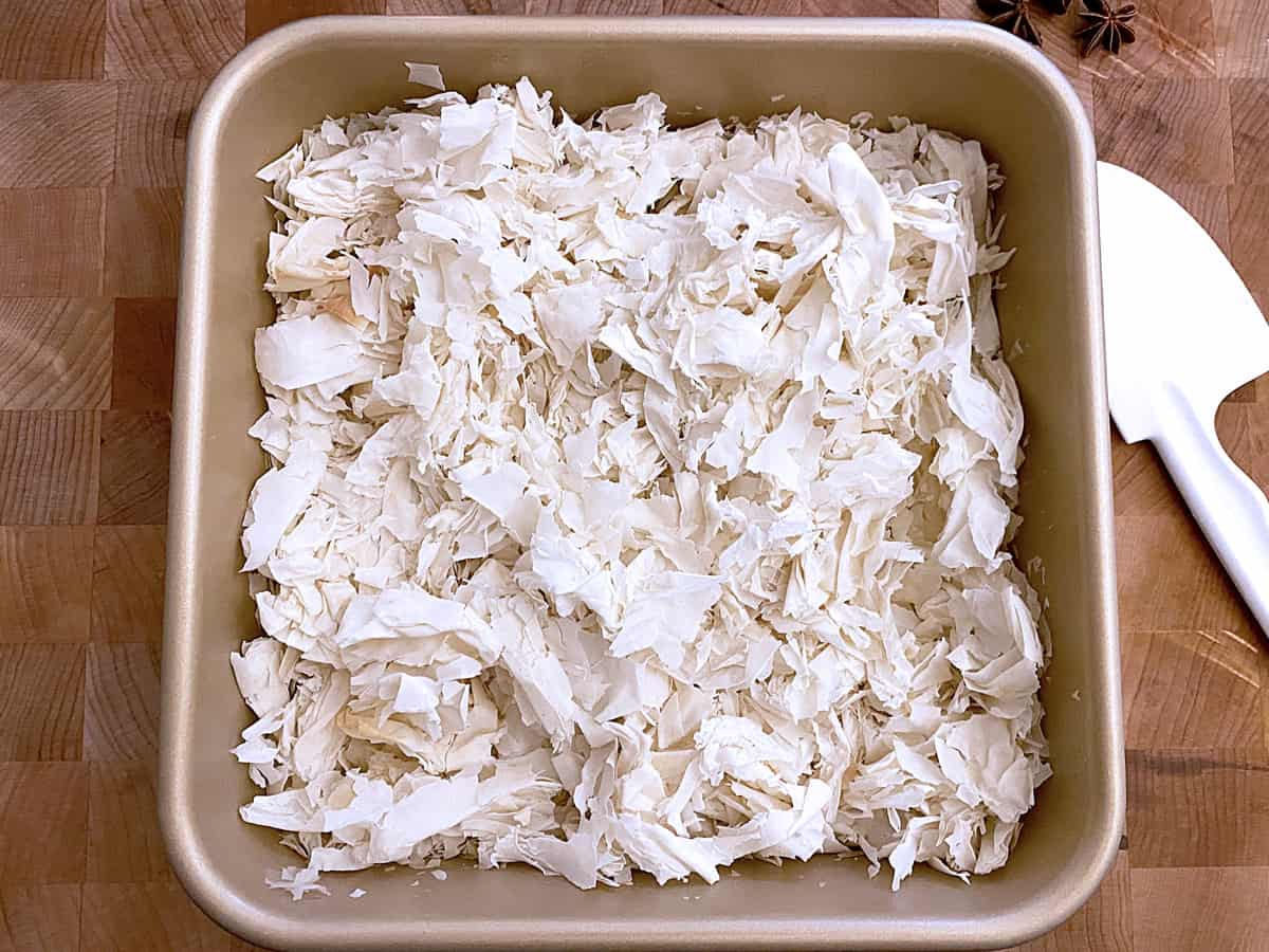 A baking pan with crumble phyllo pieces inside.