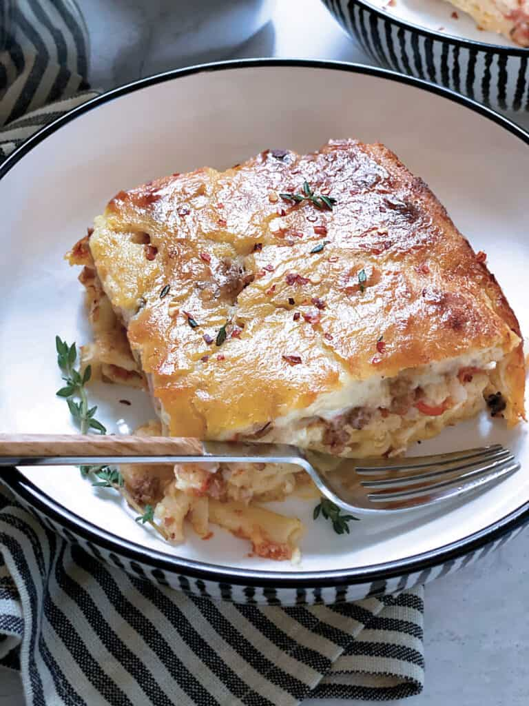 A plate with a piece of Pastitsio-Greek lasagna and a fork.