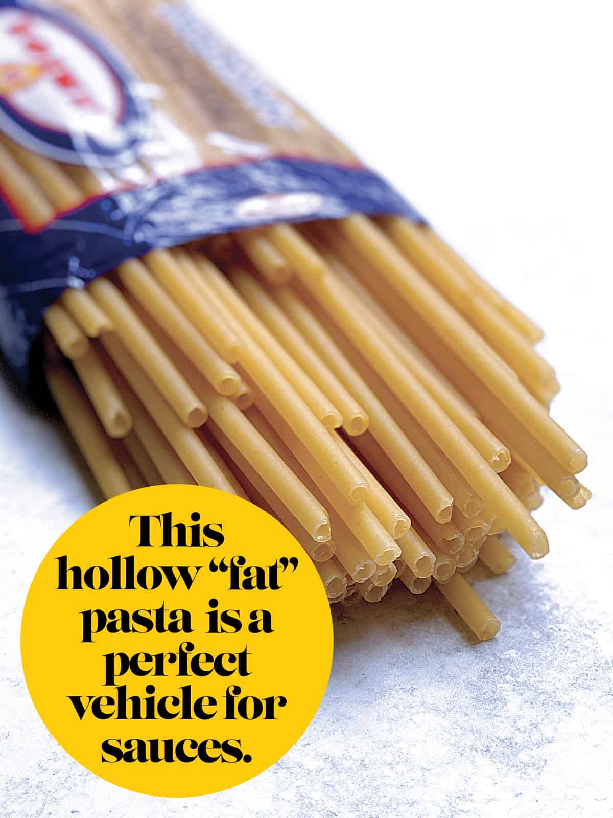 An open pack of pasta with some long macaroni showing.
