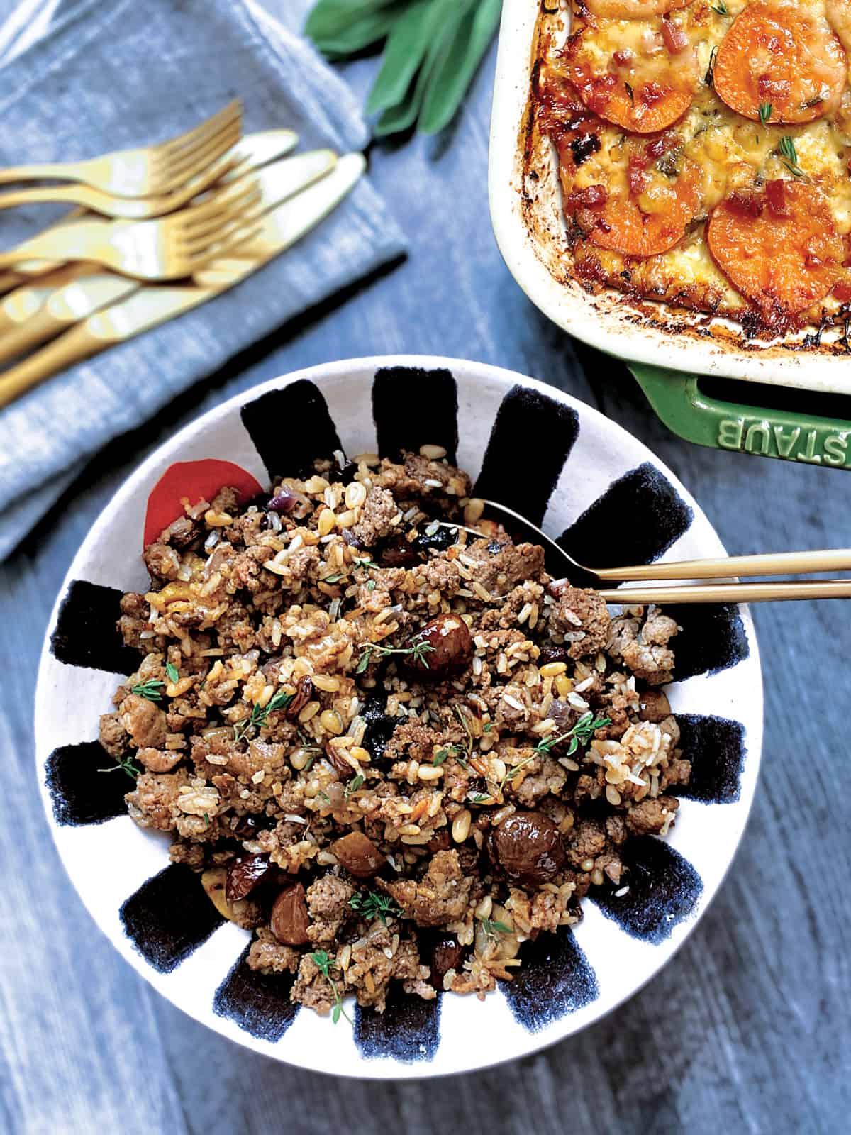 A bowl with turkey stuffing next to a sweet potato gratin.