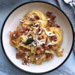 A plate with butternut squash pasta with prosciutto and goat cheese.