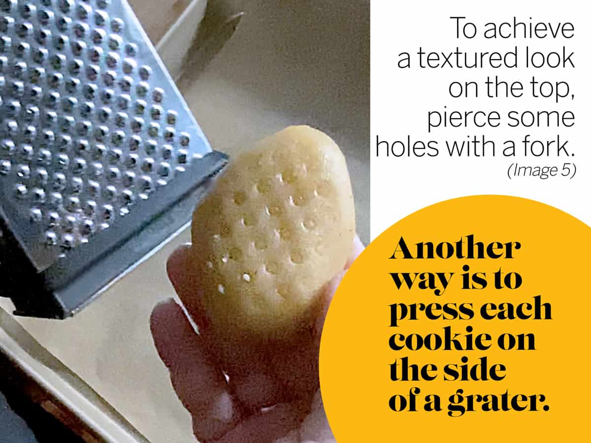 A hand holding a cookie next to a cheese grater.