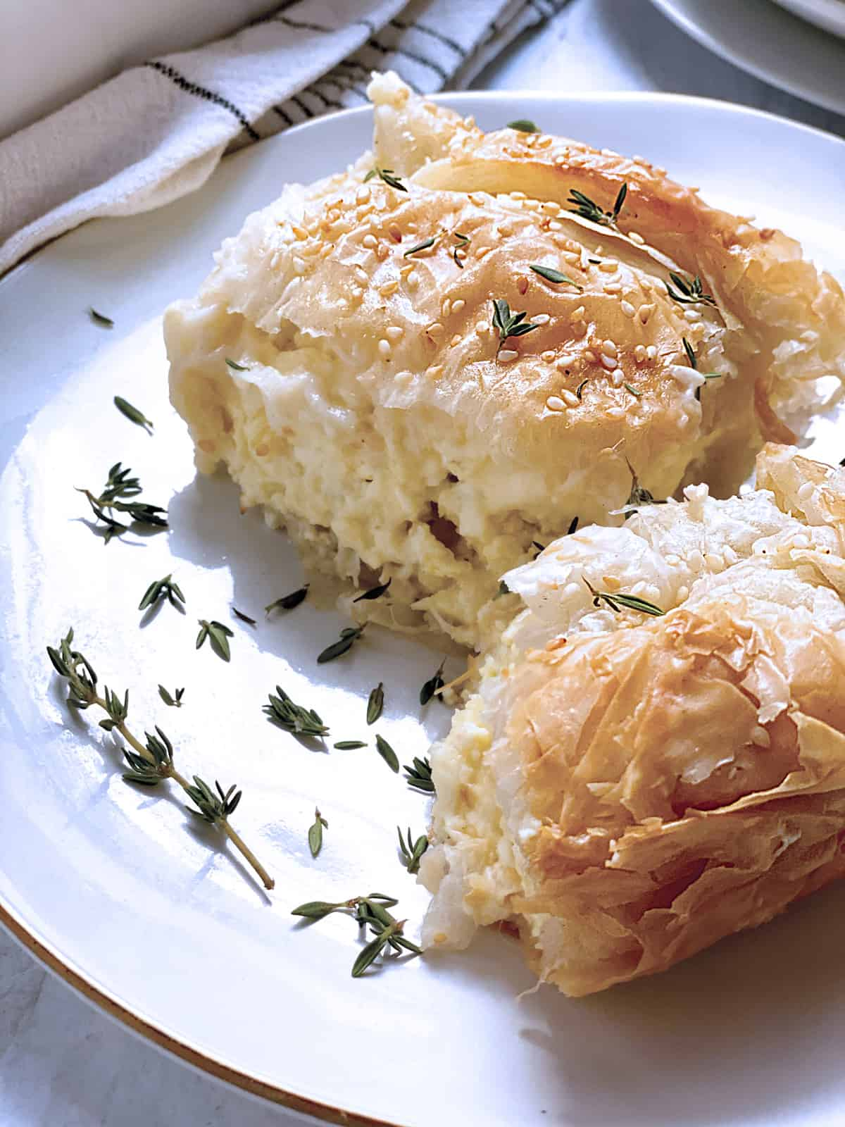 Two pieces of tiropita-cheese pie on a plate .
