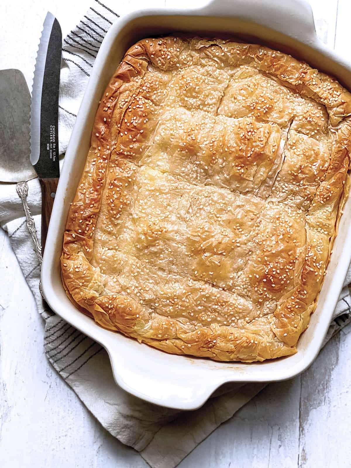 A white baking pan with Greek cheese pie-tiropita.
