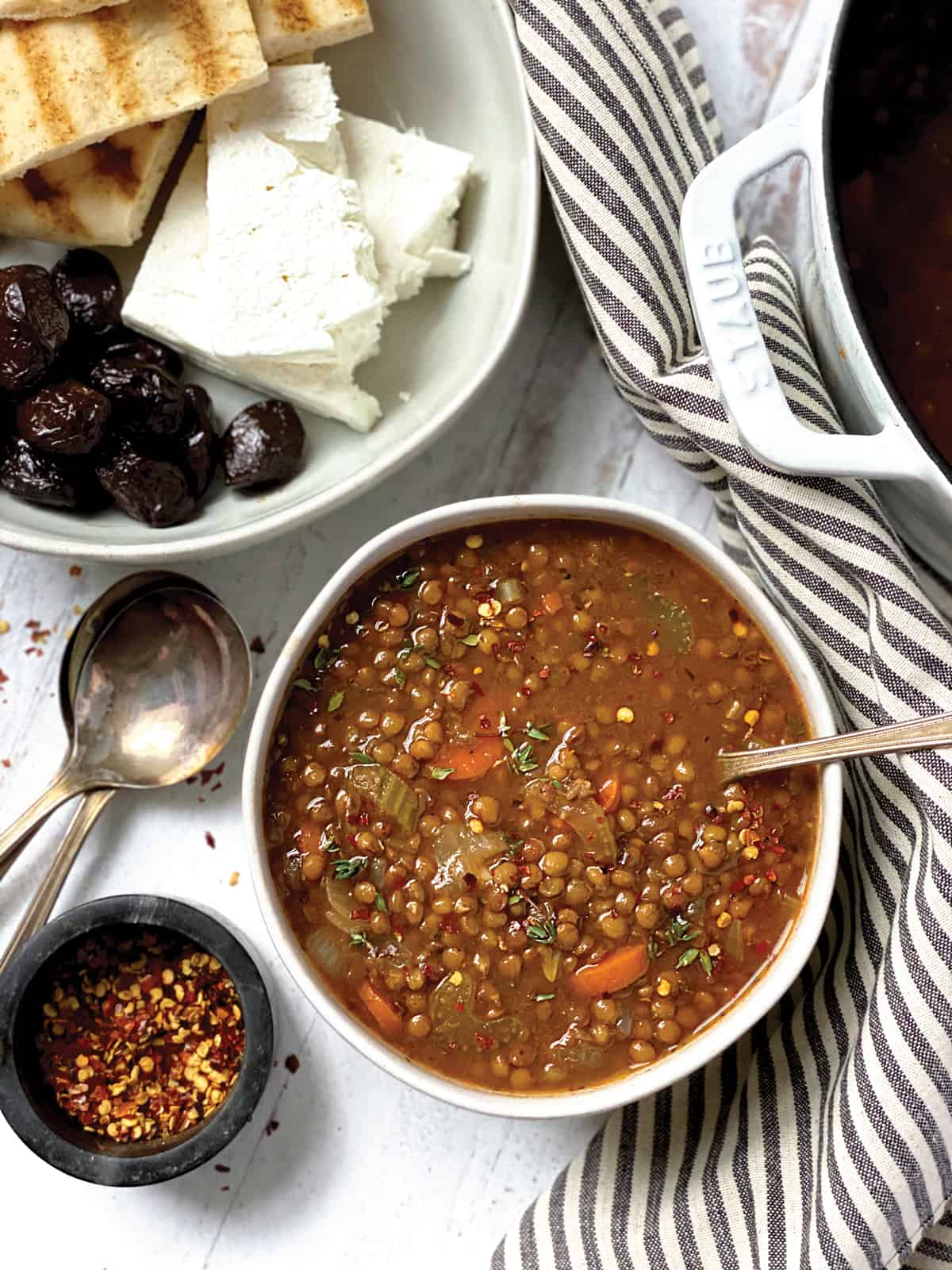 A bowl of greek lentil soup with a spoon, some spoons, a bowl of chili flakes and a plate with olives, feta and pitas at the back.