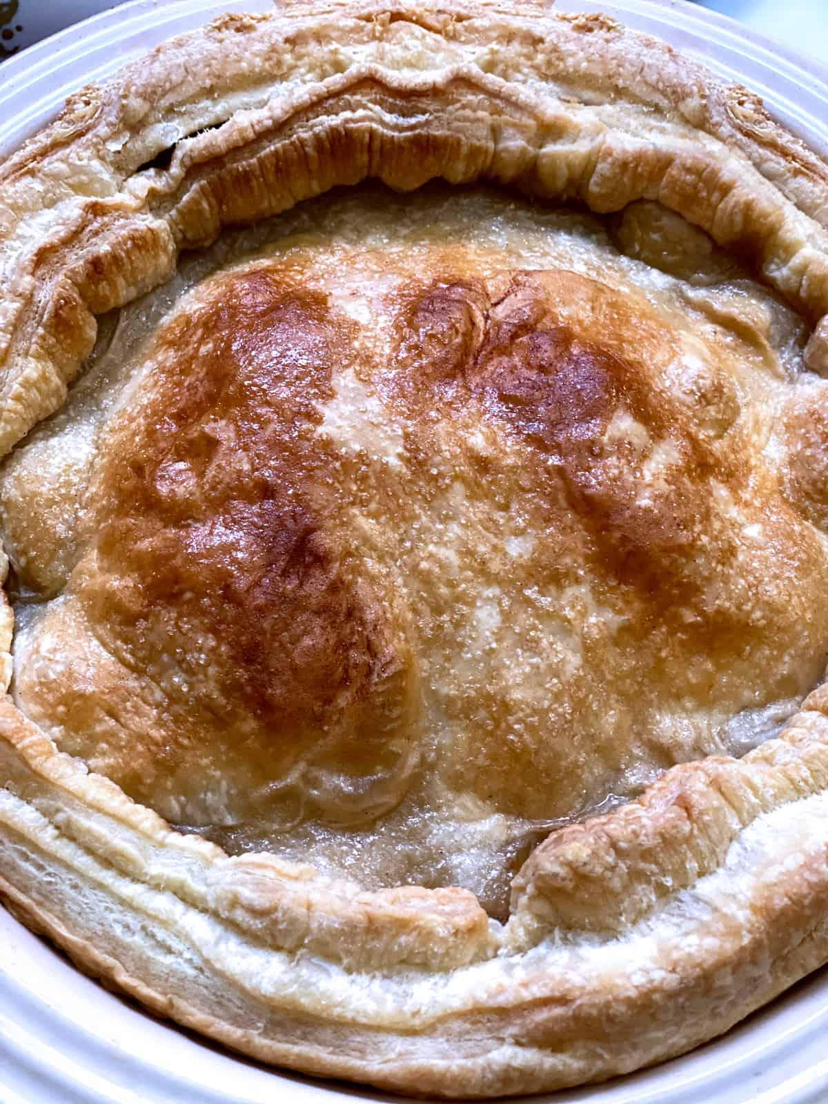 An apple pie in a round tart pan.