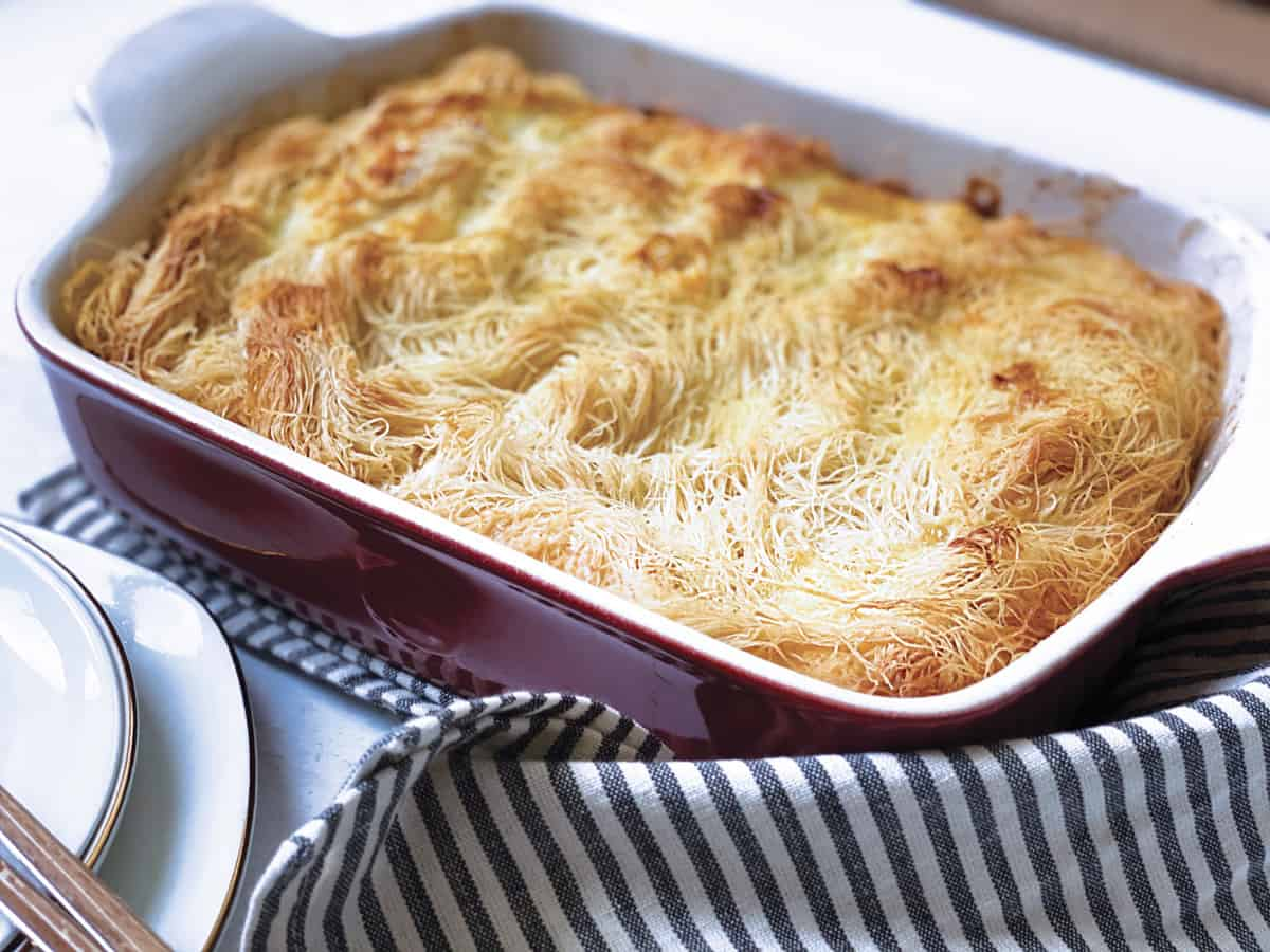 A baking pan with shredded phyllo cheese pie, some plates and a cloth napkin.