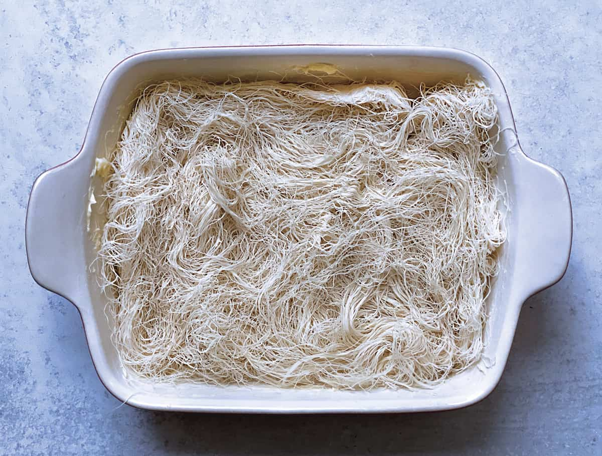 A baking pan with shredded phyllo pastry .