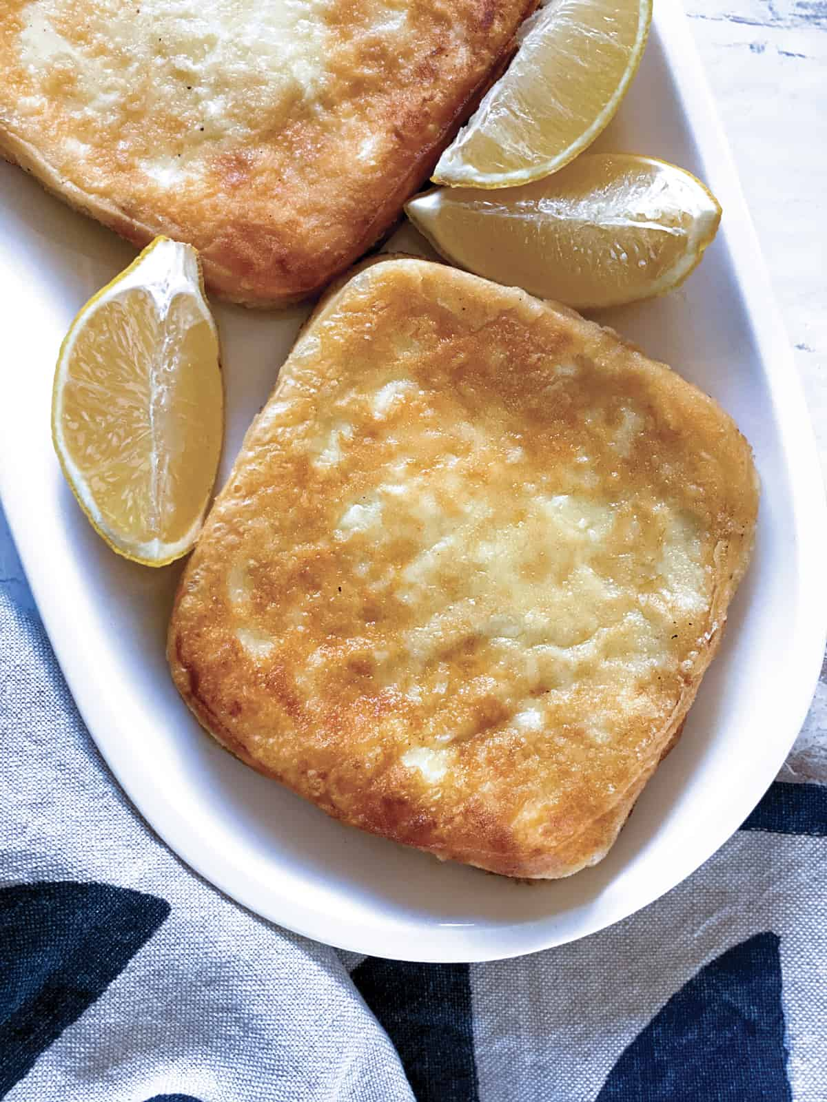 Two pieces of fried cheese on a plate, lemon wedges and a cloth napkin.