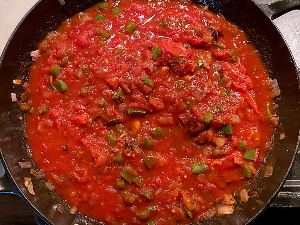 Diced onions and peppers in tomato sauce in a frying pan.