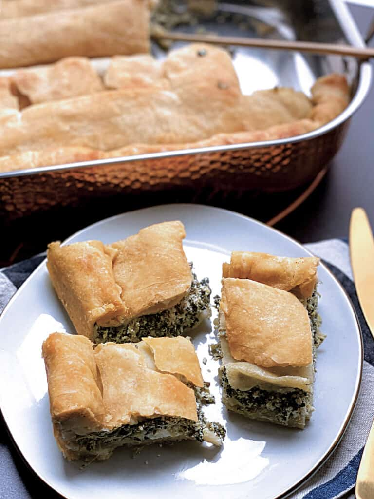 Three pieces of spanakopita on a plate, a cloth napkin and part of a knife. At the back a pan with the pie.