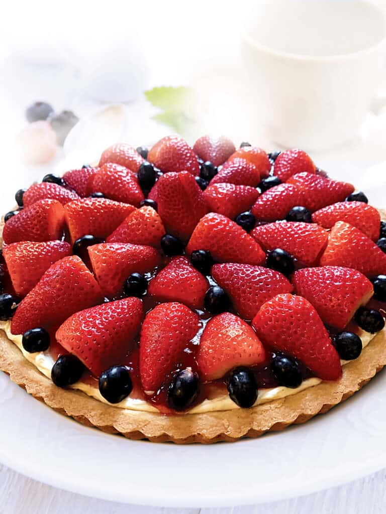 A berry tart with strawberries and blackberries on a white plate.