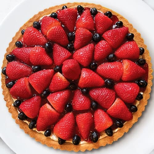 A tart with strawberries and blackberries on a white plate.