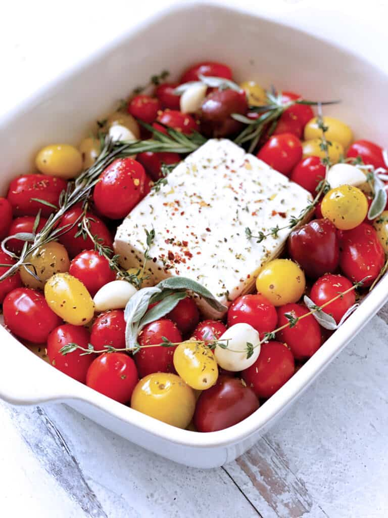 A baking pan with cherry tomatoes and a block of feta cheese in the middle.