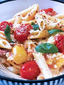 A plate with pasta with tomatoes and feta and fresh basil.