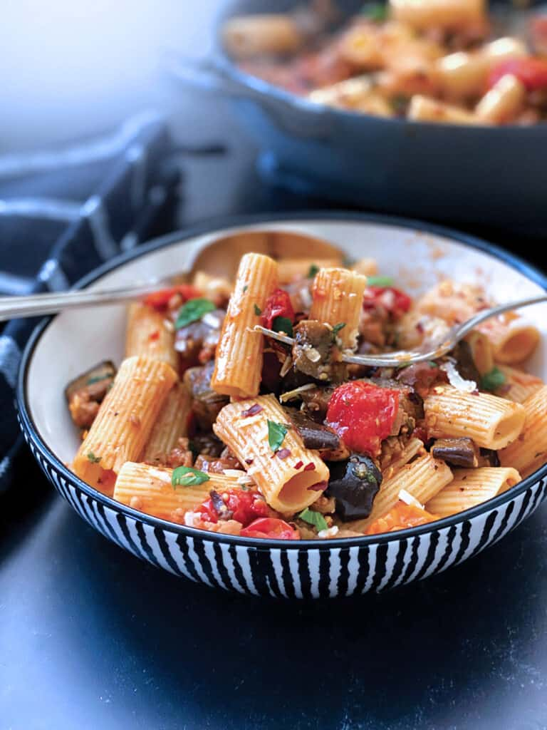 bowl with eggplant pasta, utensils. At the back A cast iron pot with eggplant pasta and a serving spoon. A cloth napkin under it.