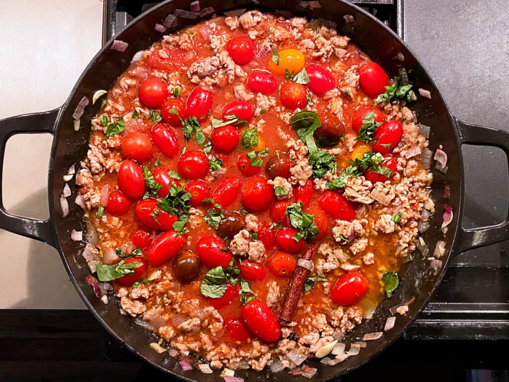 A cast iron pan with ground sausage, cherry tomatoes, fresh basil, a cinnamon stick and a bay leaf.
