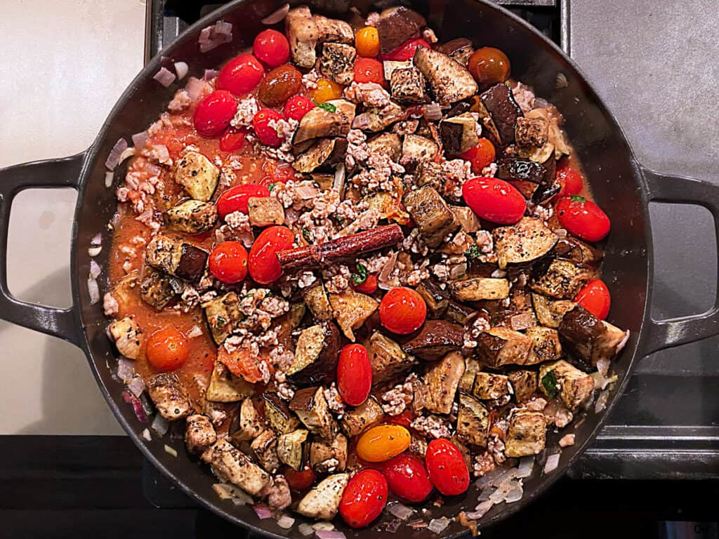 A cast iron pan with ground sausage, eggplant pieces, cherry tomatoes, fresh basil, a cinnamon stick and a bay leaf.