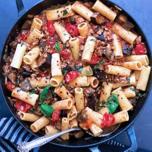 A cast iron pot with eggplant pasta and a serving spoon. A cloth napkin under it.