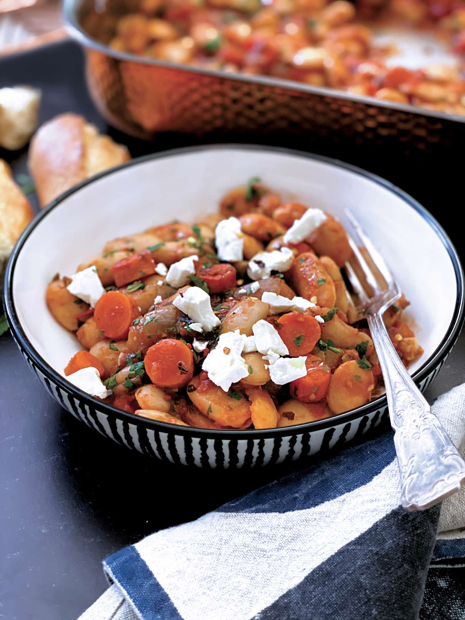 A bowl with beans, carrots, feta cheese crumbles, a fork and a large pan with beans at the back.